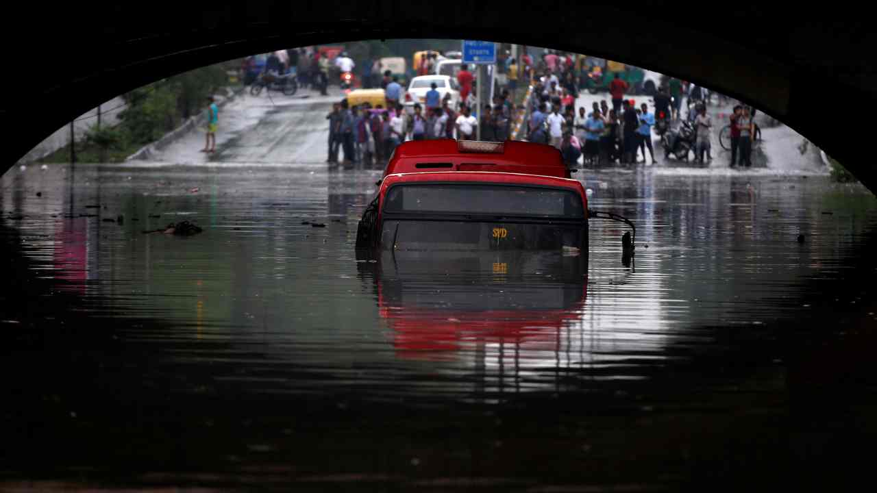 A bus is seen submerged on a flooded road under a railway bridge after heavy rains in New Delhi, India. (Reuters)