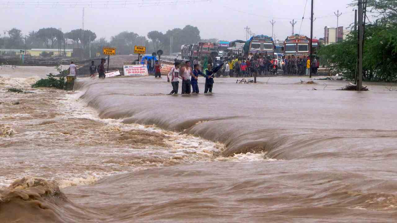 People make way through flood waters on the Una-Veraval highway after heavy rains, in Una town of Gir Somnath district. (PTI)