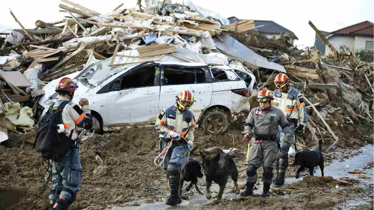 Firefighters with rescue dogs search for missing people after heavy rain hit southwestern Japan, in Kumano town, Hiroshima prefecture. Rescuers in southwestern Japan dug up more bodies as they searched for dozens still missing after heavy rains caused severe flooding and left residents to return to their homes unsure where to start the cleanup. (AP/PTI)