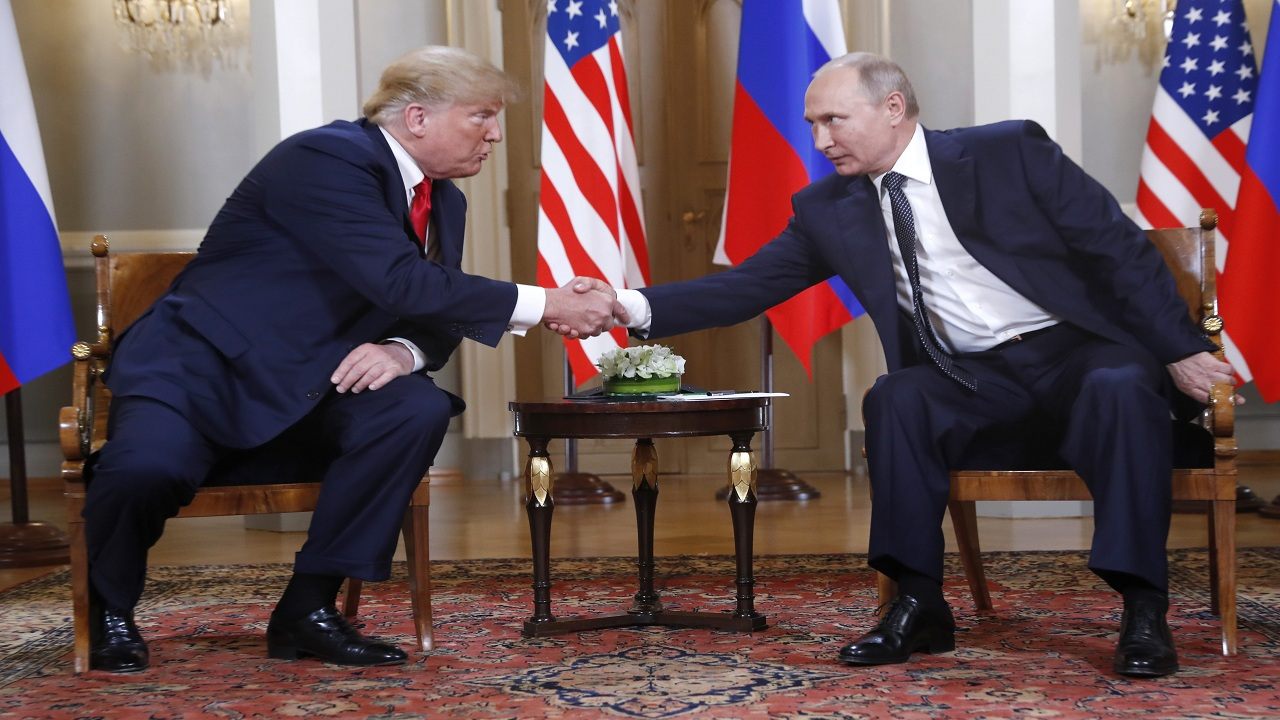 U.S. President Donald Trump, left, and Russian President Vladimir Putin shake hands at the beginning of a meeting at the Presidential Palace in Helsinki, Finland, Monday. (Image: PTI).