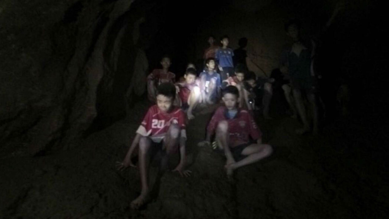 This photo released by Tham Luang Rescue Operation Center, shows the boys and their soccer coach as they were found in a partially flooded cave, in Mae Sai, Chiang Rai, Thailand. The 12 boys and coach found after 10 days, are mostly in stable medical condition and have received high-protein liquid food, officials have said, though it is not known when they will be able to go home. (Image: AP/PTI)