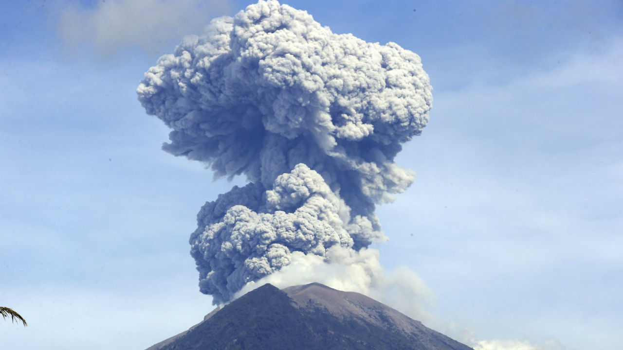 Mount Agung spews ash and smoke in Karangasem, Bali, Indonesia. The volcano on the Indonesian tourist island of Bali erupted on Monday evening, ejecting a 2,000-meter-high column of thick ash and hurling lava down its slopes. (Image: AP/PTI)