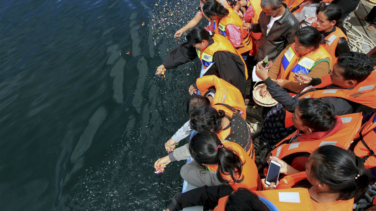 Relatives of the victims of the ferry that sank on June 18 scatter flowers during a prayer on a ship on Lake Toba, North Sumatra, Indonesia. Indonesia has stopped searching in one of the world's deepest lakes for the bodies of dozens of victims of the ferry sinking two weeks ago. (Image: PTI)