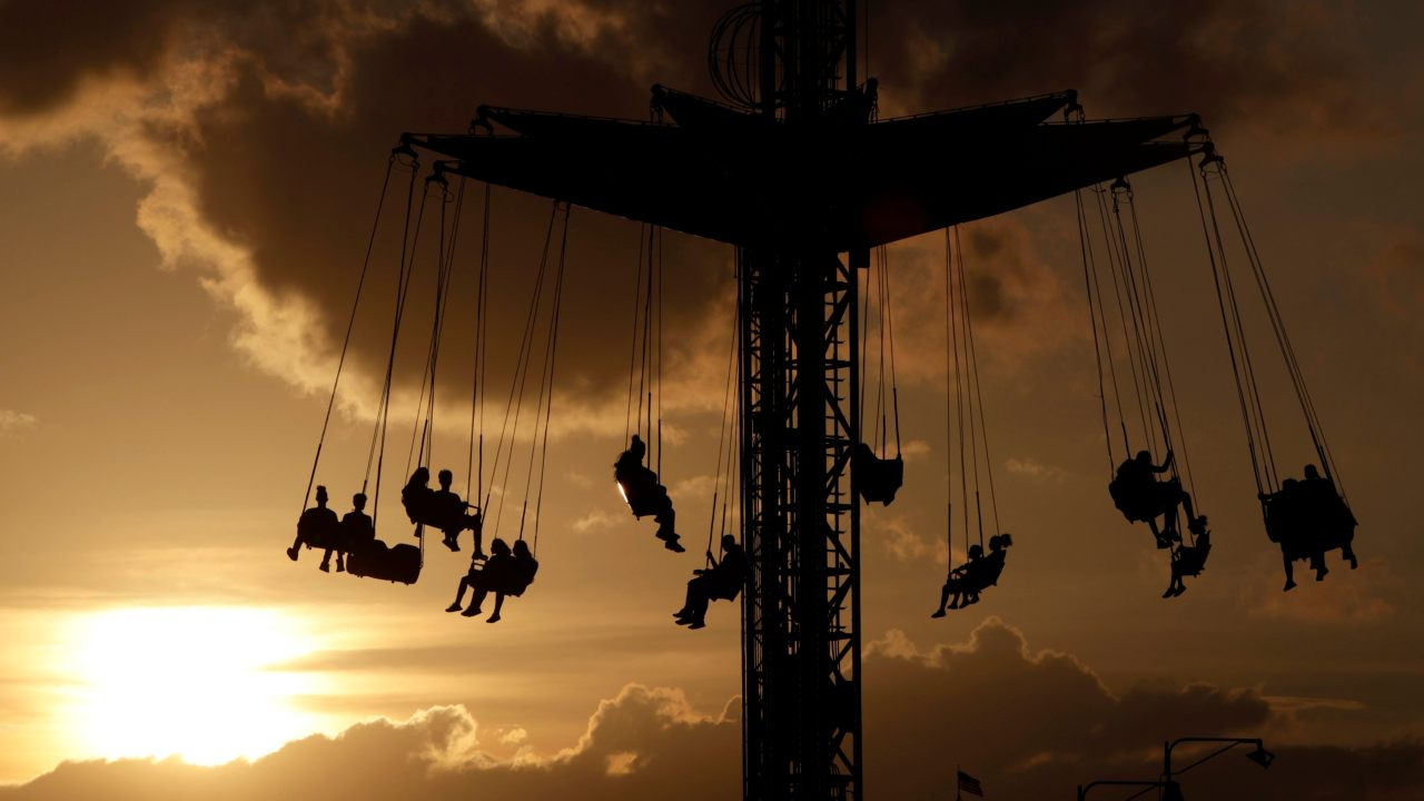 The sun begins to set behind fairgoers hanging from the Sky Flyer ride at the State Fair Meadowlands carnival in East Rutherford. (Image: AP/PTI)