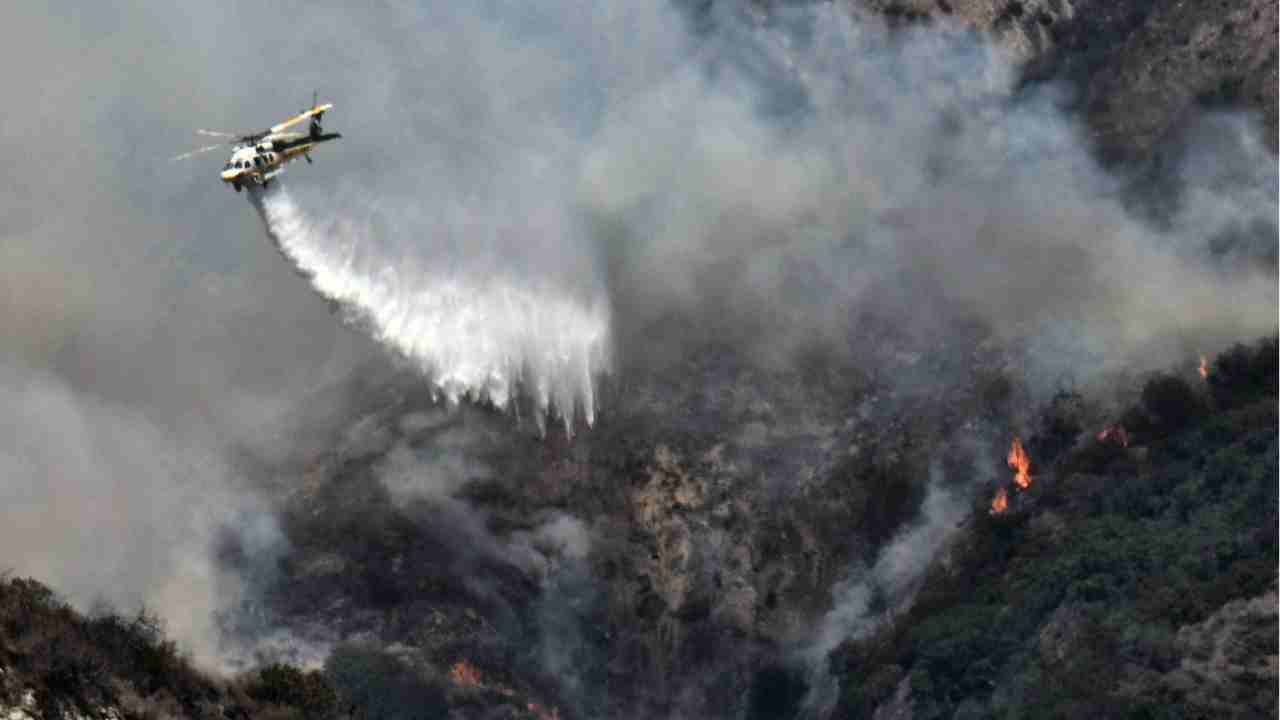 A Los Angeles County Fire Department helicopter drops water on a brush fire that erupted on a mountainside above suburban Burbank, Calif. Burbank police ordered evacuations in the Wildwood Canyon area and sent officers door to door in the area. It was one of many fires burning in California that forced firefighters to work in stifling heat. (AP/PTI)
