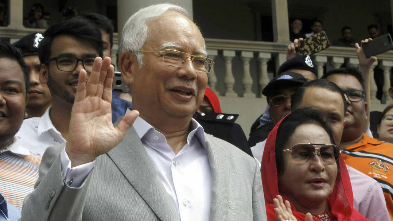 Former Malaysian Prime Minister Najib Razak and his wife Rosmah Mansor wave to their supporters as they exit the High Court of Malaya, in Kuala Lumpur, Malaysia. Najib was earlier charged last with criminal breach of trust and corruption, two months after a multibillion-dollar graft scandal at a state investment fund led to his stunning election defeat. (AP/PTI)