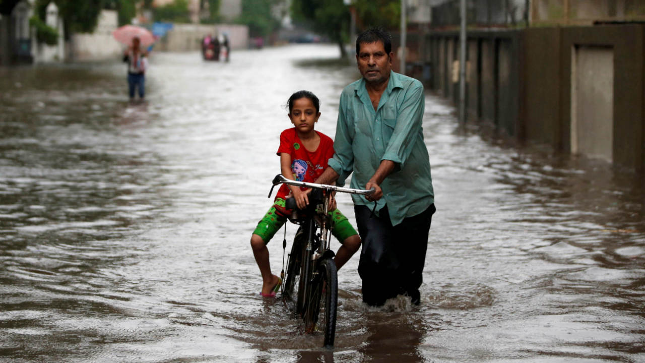 A man pushes a bicycle with a girl through a waterlogged street, after heavy rain in Ahmedabad.(Photo: Reuters)