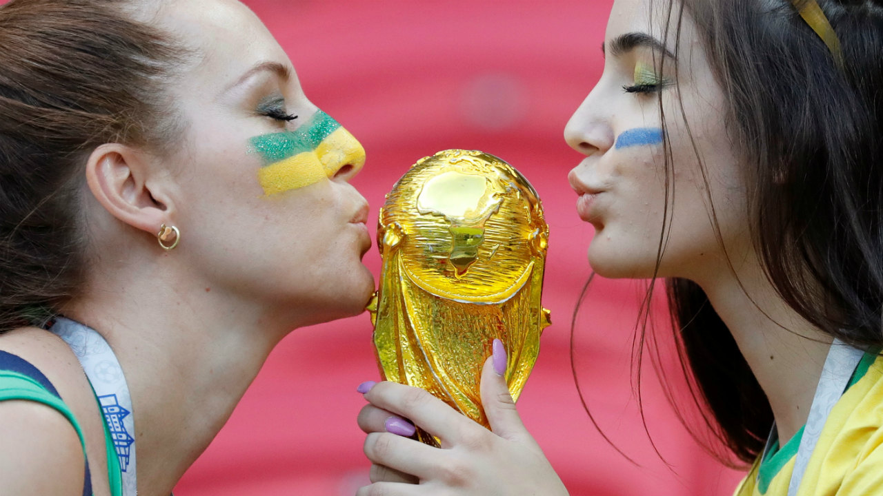 Brazil fans kiss a replica of the World Cup trophy before the match. (Image – Reuters)