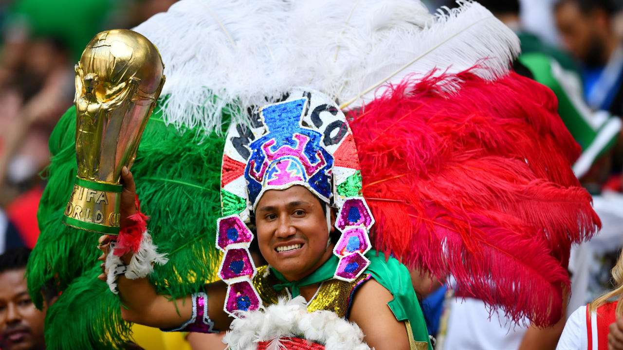 A Mexico fan, with a replica of the World Cup trophy. The Mexican fans were in full voice and came out in colourful costumes. (Image: Reuters)