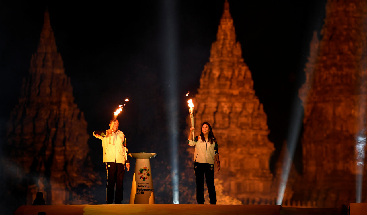 Indonesian badminton legend Susi Susanti (R) holds a flame from India as former tennis player Yustedjo Tarik (L) holds a flame from the Mrapen eternal flame before uniting them in a cauldron during the 2018 Asian Games Torch Relay ceremony at Prambanan Temple complex, Yogyakarta (Reuters)