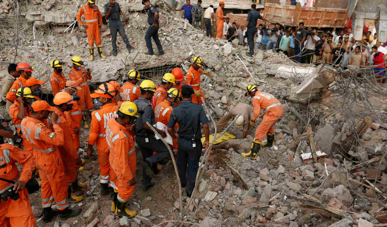 Rescue workers carry the body of a victim at the site of a collapsed residential building at Shah Beri village in Greater Noida, National Capital Region, India. (Reuters)