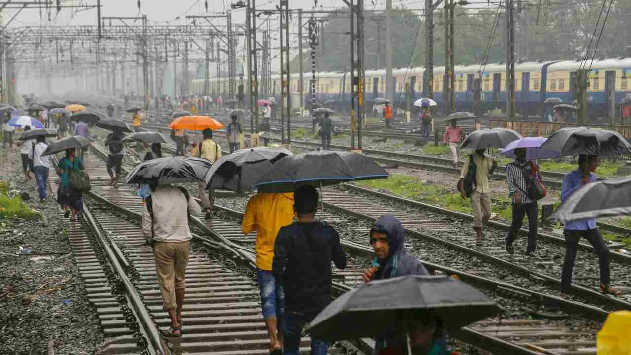 People walk on the tracks as heavy rains hit the local train services on the Central Line, in Thane on Tuesday. (PTI)