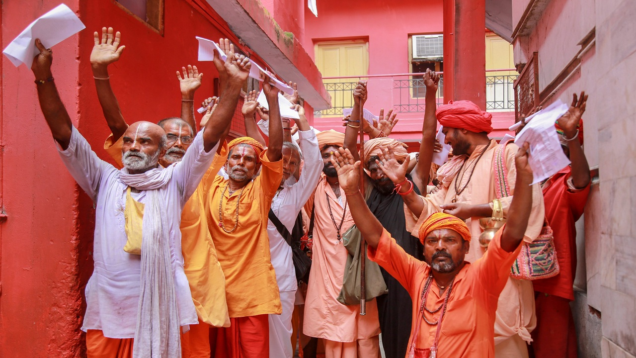 Sadhus chant religious slogans while standing in a queue to get themselves registered for the Amarnath Yatra, at a base camp, in Jammu. (Image: PTI)