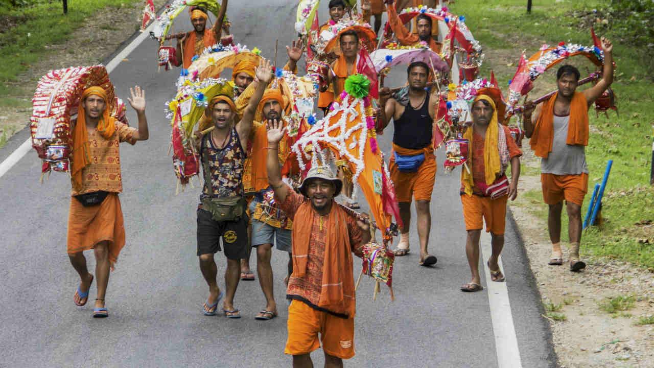 Kanwariyas chant religious slogans as they walk towards Haridwar carrying 'Kanwar' on their shoulder, in Ramnagar. (PTI)