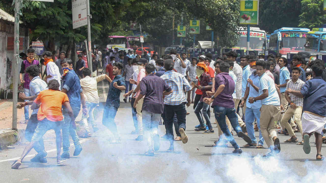 Police personnel use tear gas to disperse ABVP workers during a protest march, in Kannur. (PTI)