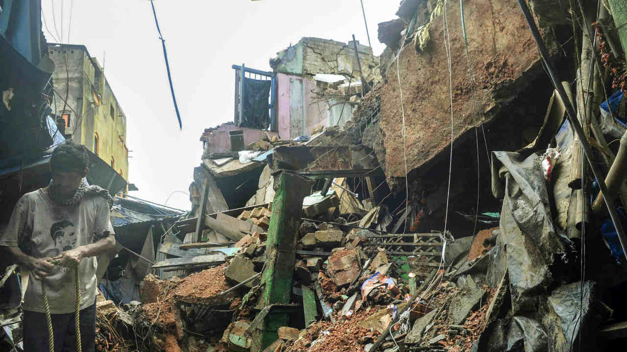 A person walks through the debris after a portion of a dilapidated two-storeyed building collapsed at Sealdah area following monsoon rains, in Kolkata. Atleast two people died in the accident and several were injured. (PTI)