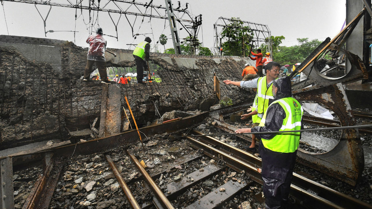 Rescue workers clear the debris of Gokhale foot overbridge that collapsed on the Western Railway tracks, at Andheri station following heavy rain, in Mumbai. (Image: PTI)
