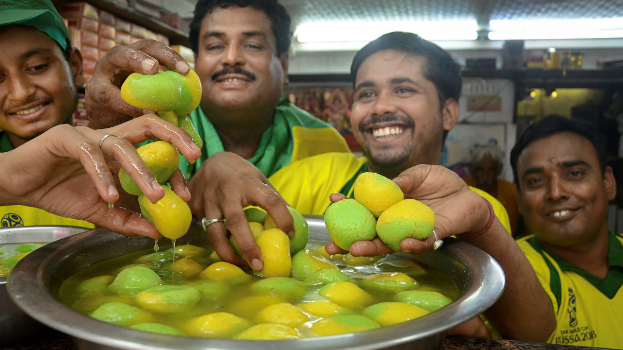 Confectioners wear Brazil football jersey as they celebrate with 'roshogulla', coloured in the Brazil colours, after Brazil won the match against Mexico, in Kolkata. (Image: PTI)