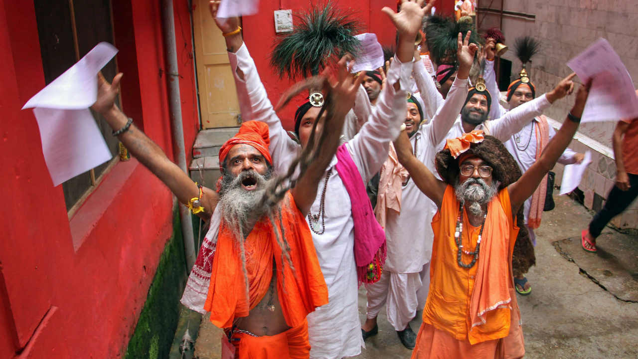 Sadhus chant religious slogans while standing in a queue to get themselves registered for Amarnath Yatra at a base camp, in Jammu. (PTI)