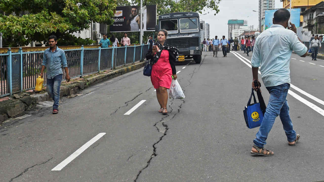 A woman walks along the crack developed over the bridge at the Grant Road station, in Mumbai. Cracks were found on a bridge at the Grant Road station in south Mumbai, hours after an over- bridge collapsed at a railway station in suburban Andheri. (PTI)