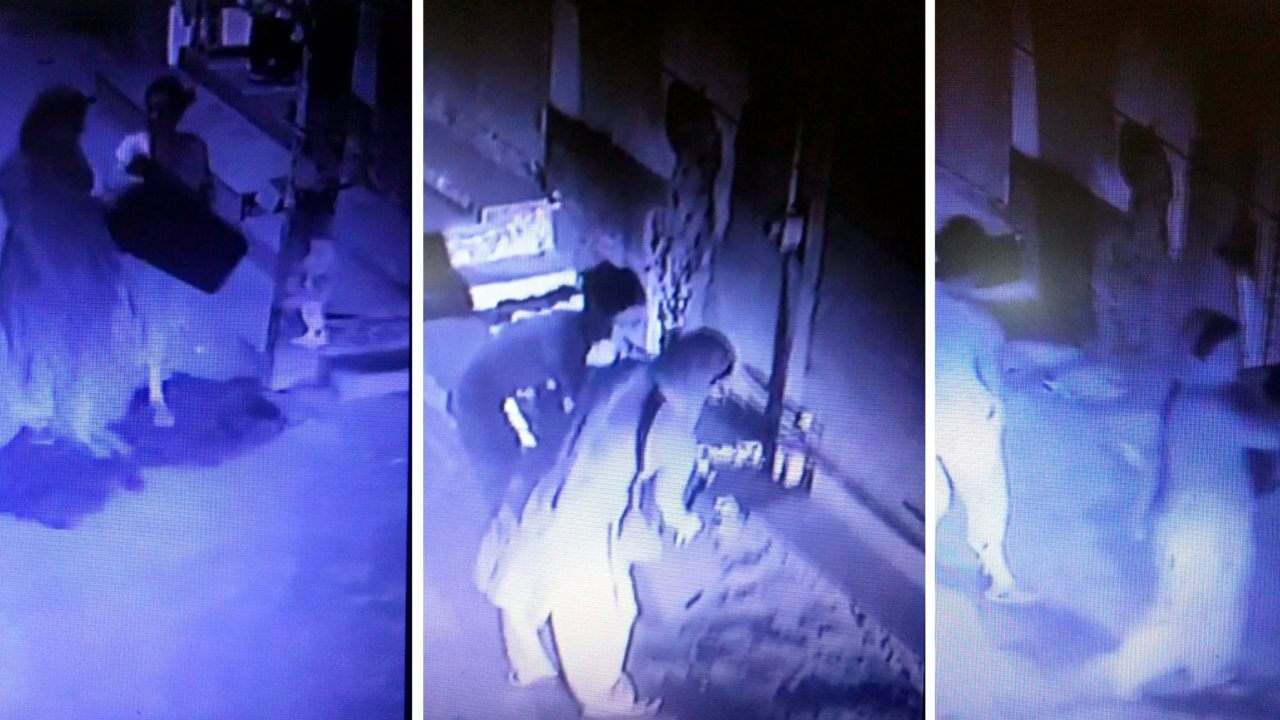 A screengrab from a CCTV camera with a view of the entrance of the Chundawat house is seen members of the family carrying stools , later used in mass hanging which rendered 11 members dead, at Burari area in New Delhi. (Image: PTI)