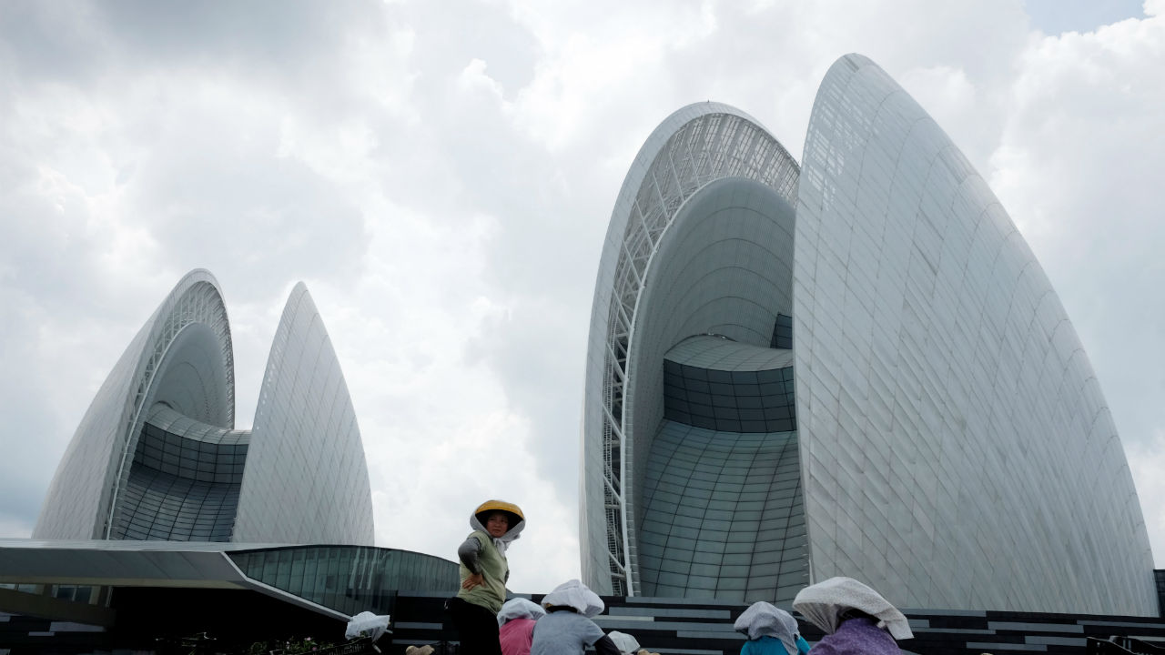 Workers plant flowers in front of Zhuhai Opera House in Zhuhai, China. (REUTERS)
