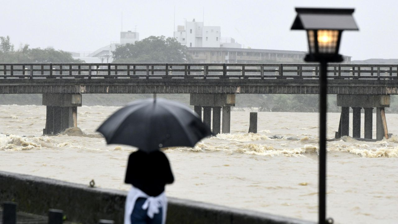 A local resident watches Togetsu Bridge and swollen Katsura River, caused by a heavy rain, in Kyoto, western Japan. (Image: Reuters)