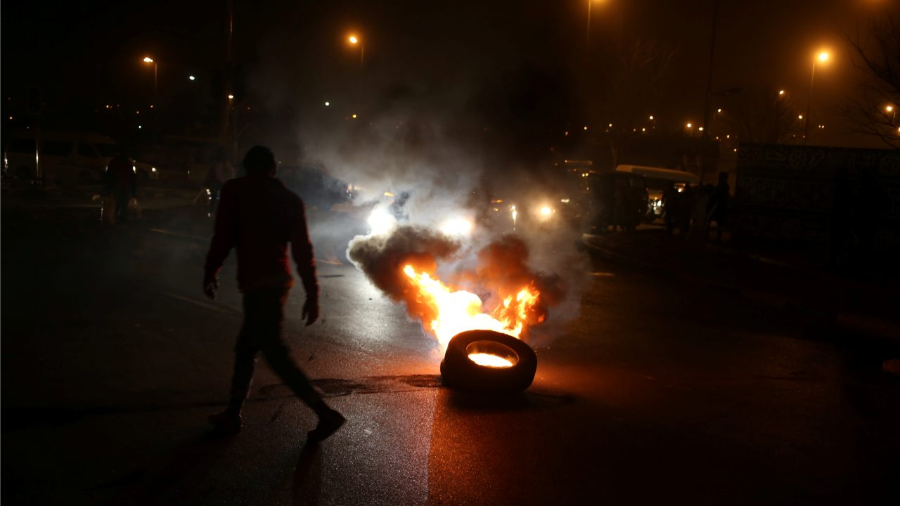 A man walks past a burning tyre during a protest against electricity cuts in Klipspruit Soweto, Johannesburg, South Africa. (Image: Reuters)