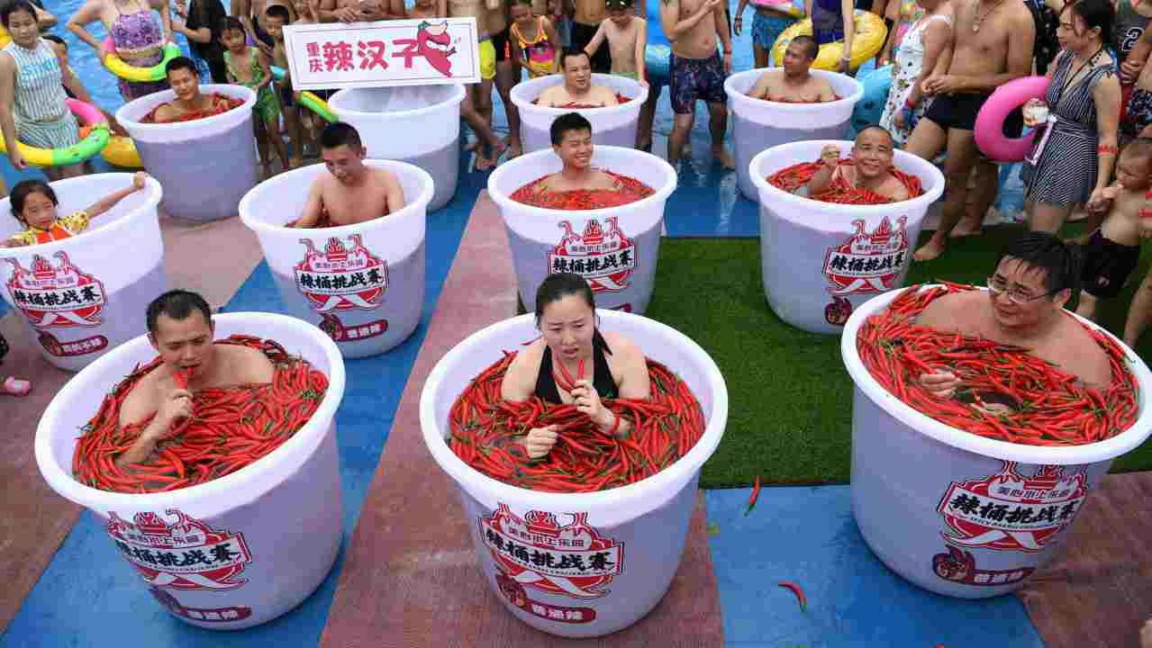 Participants take a bath in barrels filled with chilli peppers during the Spicy Barrel Challenge contest inside a water park in Chongqing, China. (Reuters)