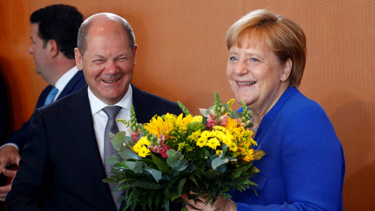 Chancellor Angela Merkel receives from German Finance Minister Olaf Scholz a bouquet of flowers for her yesterday's 64th birthday at the weekly cabinet in Berlin, Germany, July 18, 2018. (REUTERS)
