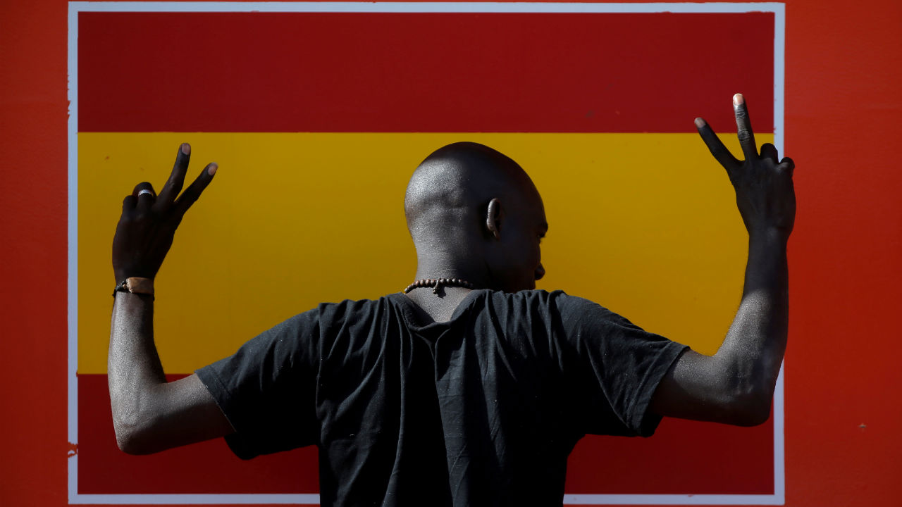 A migrant, intercepted aboard a dinghy off the coast in the Strait of Gibraltar, gestures next to a Spanish flag on a rescue boat after arriving at the port of Algeciras, southern Spain. (REUTERS)