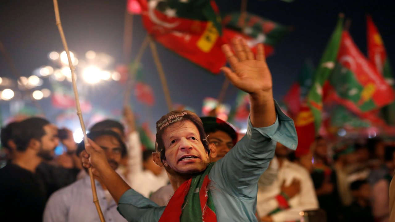 A supporter of Imran Khan, chairman of the Pakistan Tehreek-e-Insaf (PTI), political party, wears a mask and dance on party songs during a campaign rally ahead of general elections in Karachi, Pakistan. (Image: REUTERS)