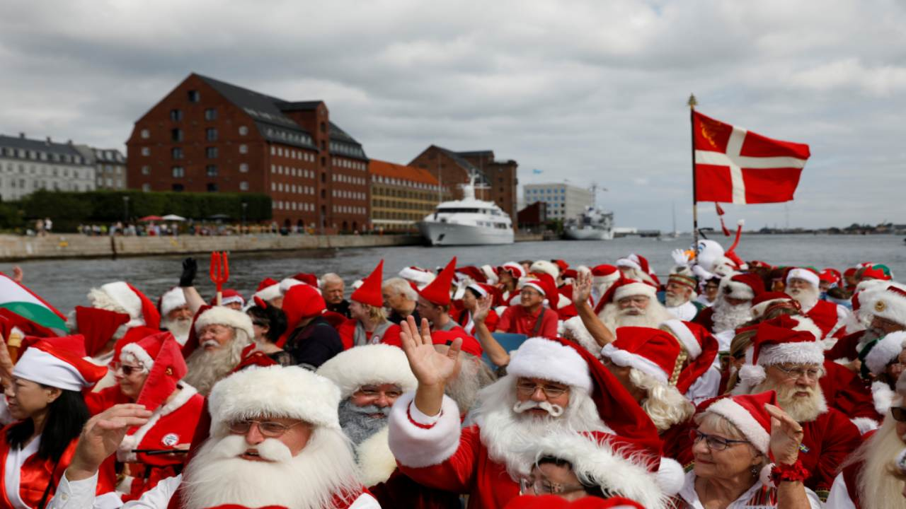 People dressed as Santa Claus wave from a canal boat as they take part in the World Santa Claus Congress, an annual event held every summer in Copenhagen, Denmark. (Image: REUTERS)