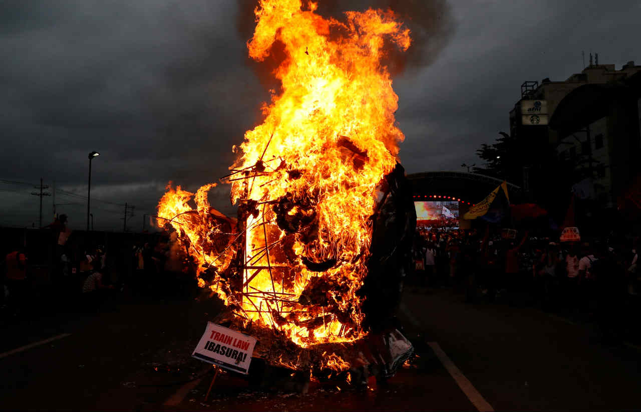 Activists burn an effigy of President Rodrigo Duterte while he delivers his State of the Nation address at the House of Representatives in Quezon city, Metro Manila, in Philippines. (REUTERS)