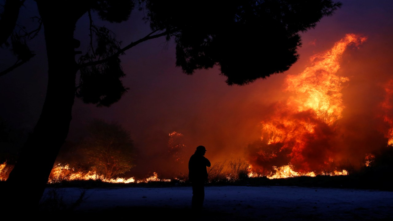 A man looks at the flames as a wildfire burns in the town of Rafina, near Athens, Greece. (Image: REUTERS)