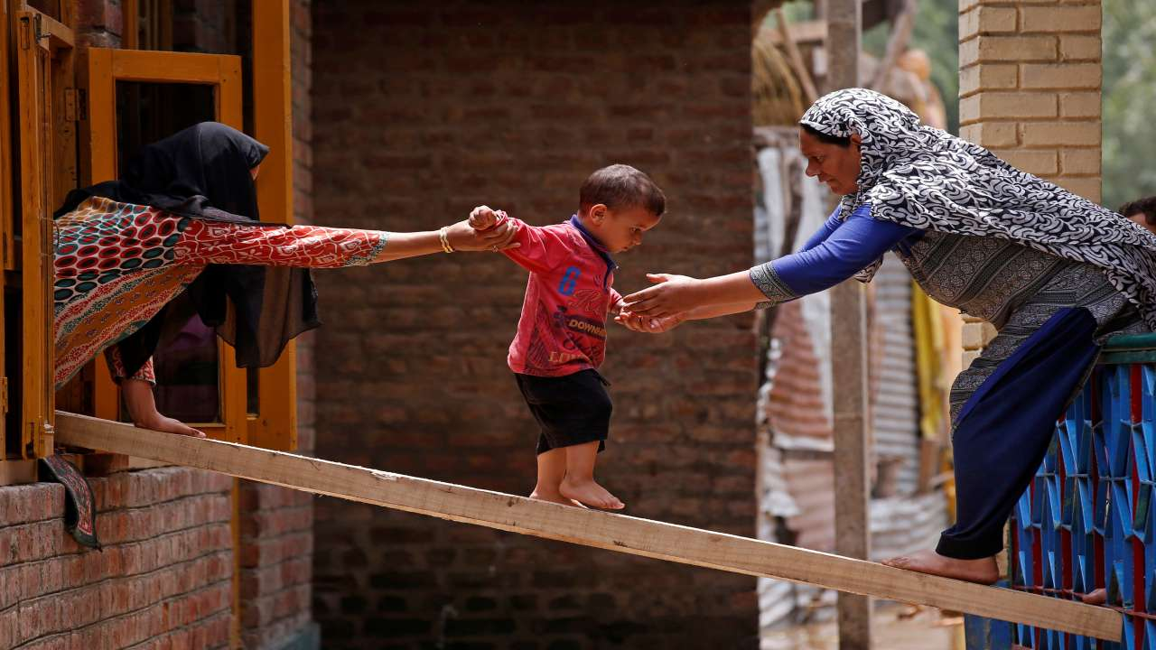 Women help a child to cross over to the other house on a wooden plank after flash floods in Tailbal, on the outskirts of Srinagar. (Image: REUTERS)