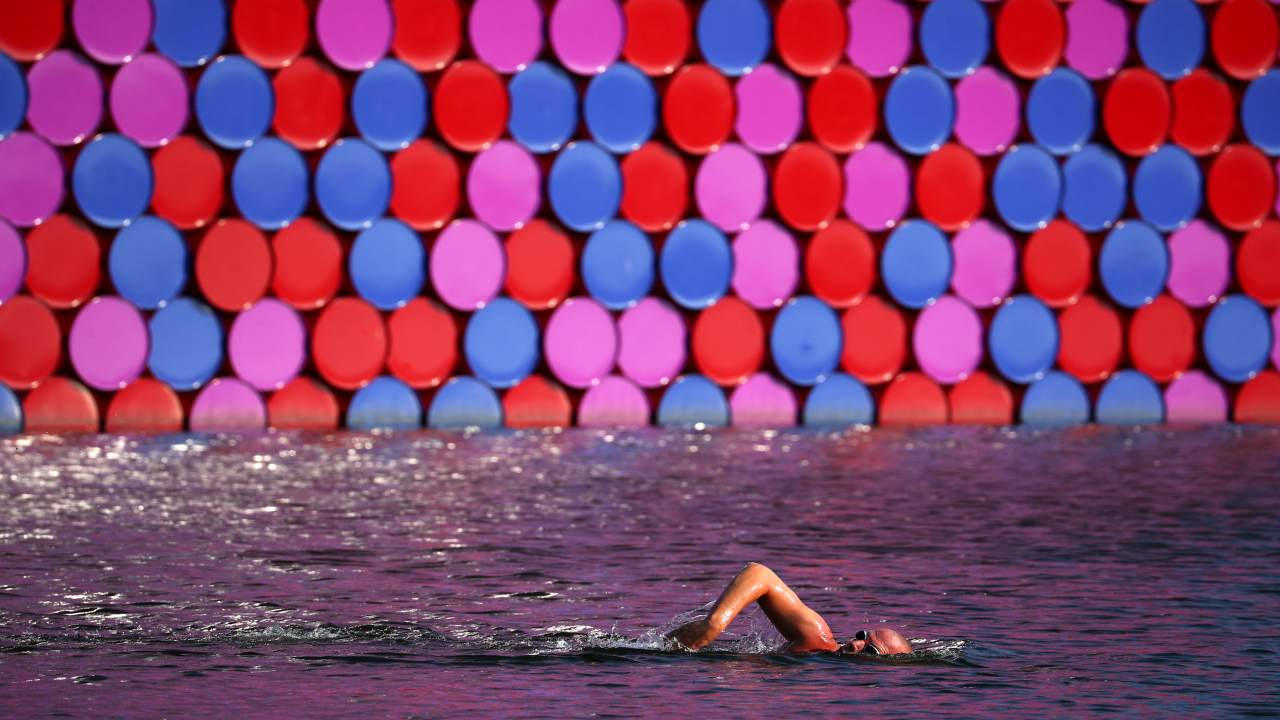"A man swims past Christo's floating sculpture ""The London Mastaba"" on the Serpentine in London. (REUTERS)"