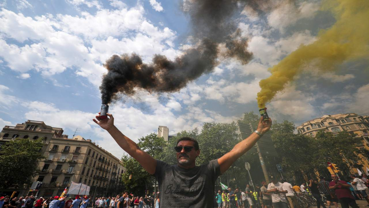 A taxi driver holds up smoke bombs during a strike against what they say is unfair competition from ride-hailing and car-sharing services such as Uber and Cabify in Barcelona, Spain. (Image: REUTERS)