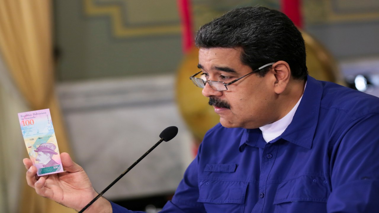Venezuela's President Nicolas Maduro holds a bank note of the new Venezuela's currency Bolivar Soberano (Sovereign Bolivar) as he speaks during a meeting with ministers at Miraflores Palace in Caracas, Venezuela. (Image: REUTERS)