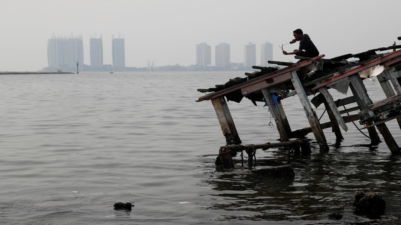A youth stands on the wreckage of a wooden boat, during fishing with a slingshot, as smog covers North Jakarta, Indonesia. (Image: REUTERS)