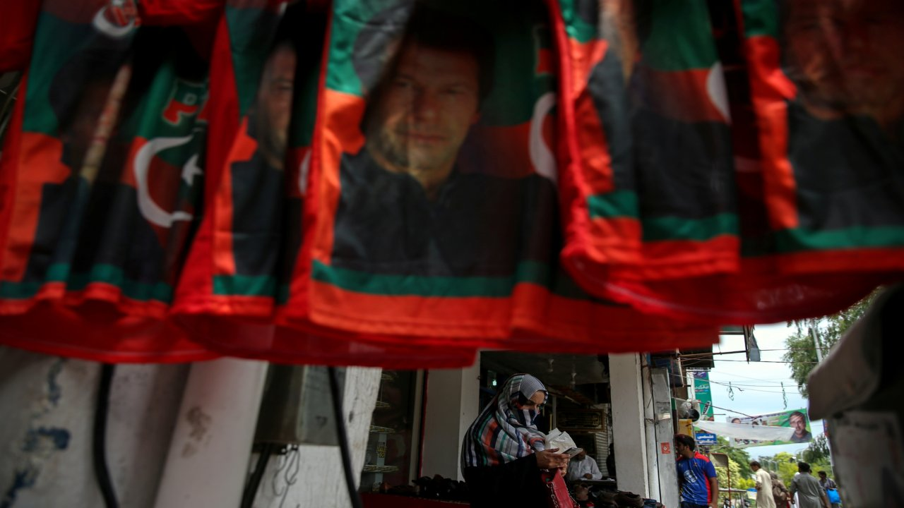A woman stands next to the t-shirts with images of Imran Khan, leader of the Pakistan Tehreek-e-Insaf (PTI), at a market, a day after general election in Islamabad, Pakistan. (Image: REUTERS)