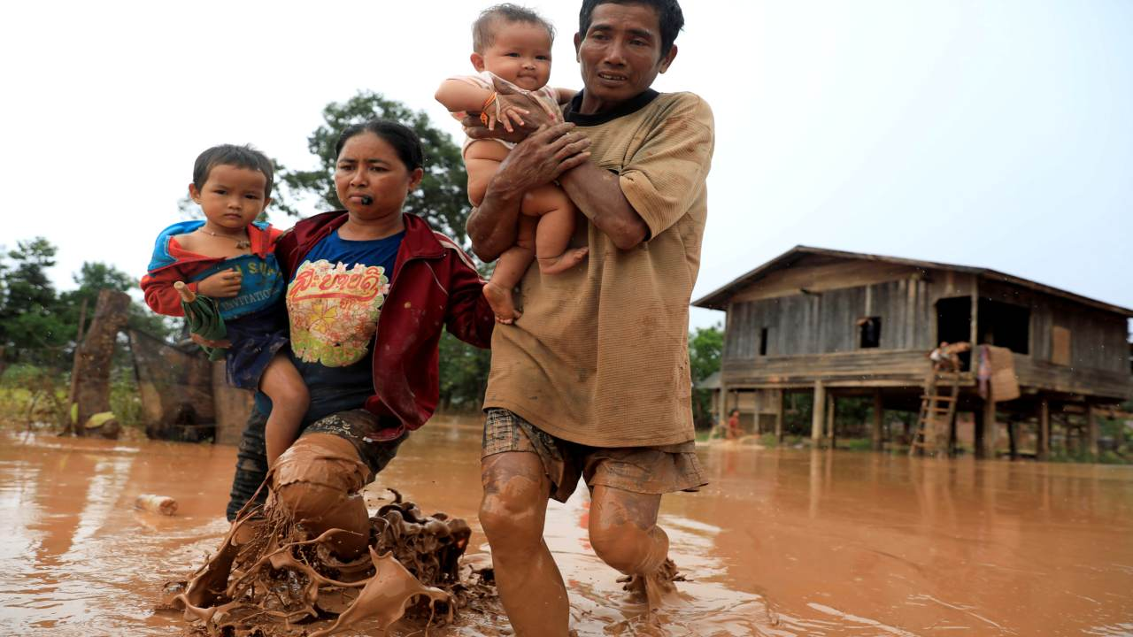 Parents carry their children as they leave their home during the flood after the Xepian-Xe Nam Noy hydropower dam collapsed in Attapeu province, Laos. (Image: REUTERS)