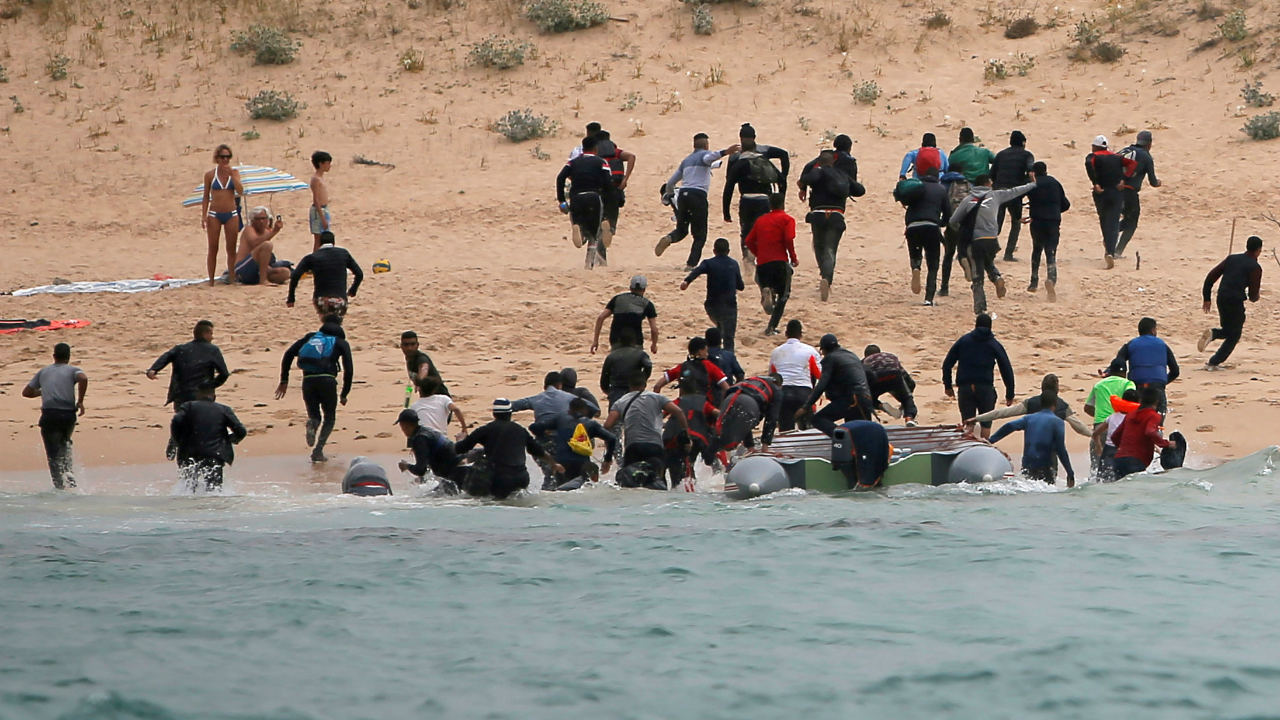 """Migrants disembark from a dinghy at """"Del Canuelo"""" beach after they crossed the Strait of Gibraltar sailing from the coast of Morocco, in Tarifa, southern Spain. (Image: Reuters)"""