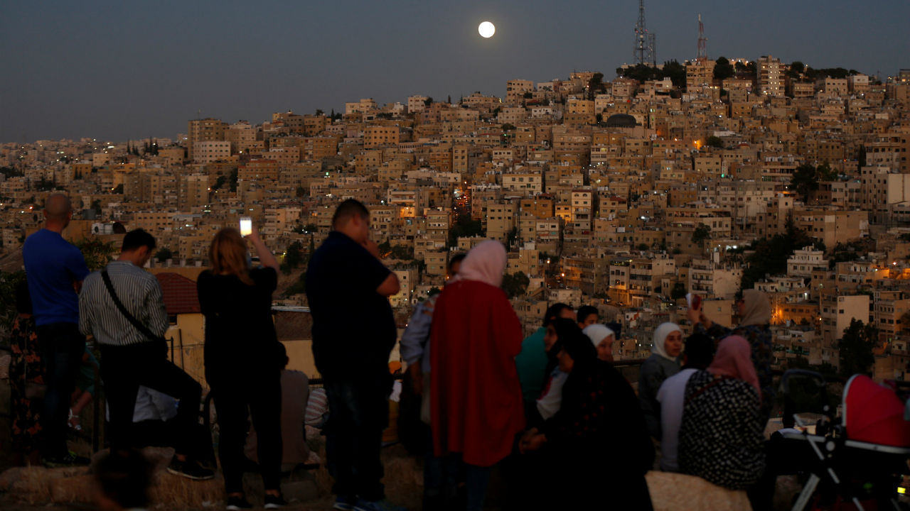 People wait for the lunar eclipse at Amman Citadel in Amman, Jordan. (Image: Reuters)