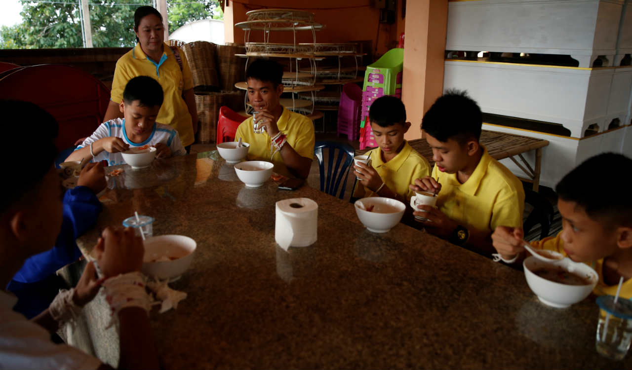 Members of a soccer team rescued from a cave eat their breakfast during a religious ceremony, in a temple at Mae Sai, in the northern province of Chiang Rai, Thailand (Reuters)