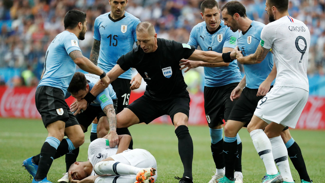 Referee Nestor Pitana separates players as France's Kylian Mbappe lies on the pitch. Mbappe went down a bit too easily following a little touch from Christian Rodriguez which infuriated the Uruguay players. The referee was quick to book both Mbappe and Rodriguez for the incident. (Image – Reuters)
