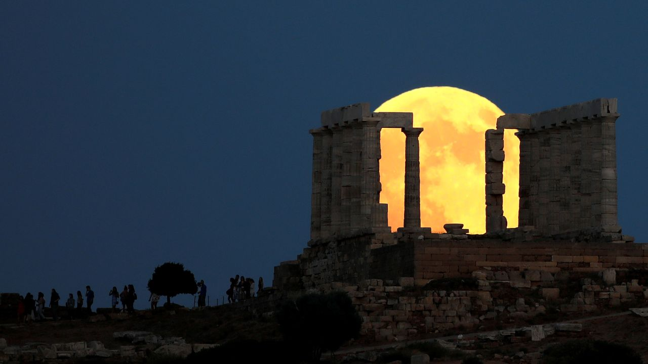 People watch a full moon rising behind the Temple of Poseidon before a lunar eclipse in Cape Sounion, near Athens, Greece. (Image Source: Reuters)