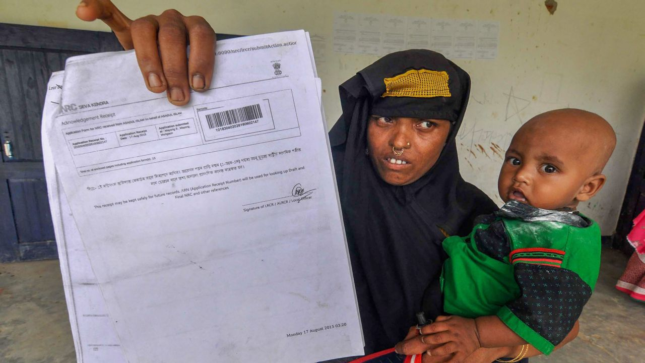 A woman shows an NRC acknowledgment receipt to check her name in the final draft of Assam's National Register of Citizens (NRC), at an NRC Seva Kendra, in Morigaon. (Image source: PTI)