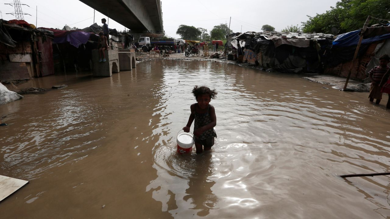A girl carries drinking water as she wades through a flooded street at a slum area after a rise in the waters of the river Yamuna. (Image source: Reuters)