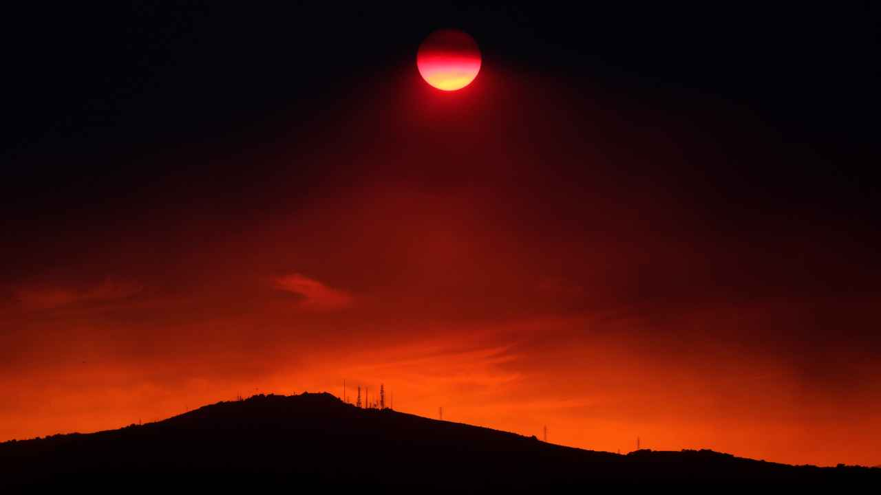 The sun sets under a cloud of smoke caused by a wildfire fanned by strong winds on the island of Evia, in Athens, Greece. (Reuters)